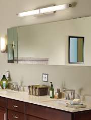 A chrome long wall light above a mirror and vanity