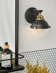 A black Wall Sconce besdie a vanity mirror
