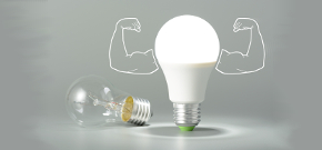 LED lamp with cartoon muscles arms stands over an old incandescent lamp