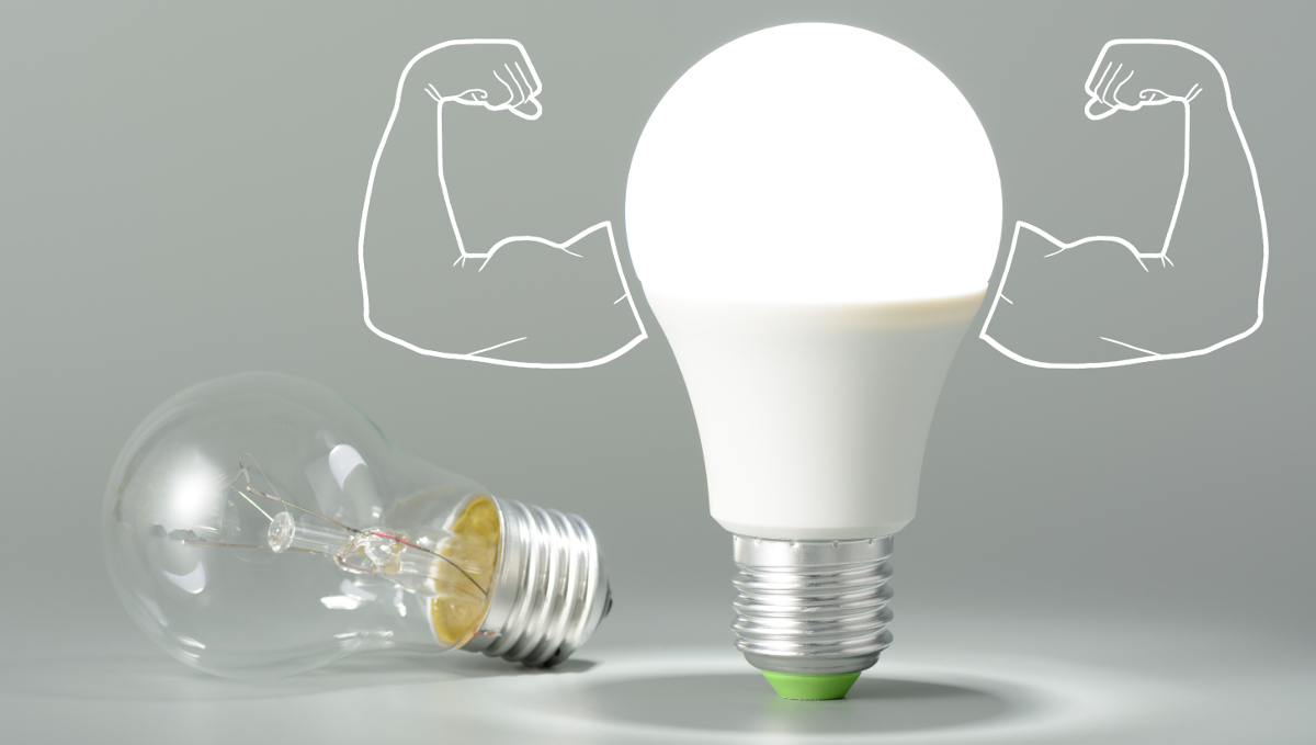 an old incandescent lamp lies on its side while an LED lamp stands next to is with cartoon muscles arms coming out of it