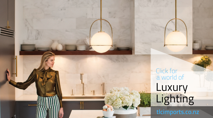 Lady in modern kitchen, shee seems happy with her two hinkley somerset pendants over a kitchen island