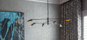 Lounge room with closeup view of balck pendant with 6 arms and gold inners on the shades